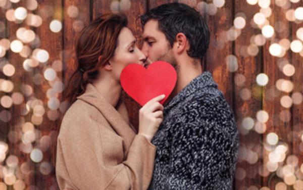 Парень с девушкой целуются. Она прикрывает их картонным сердечком
