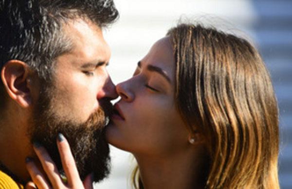 Девушка нежно целует бородатого мужчину