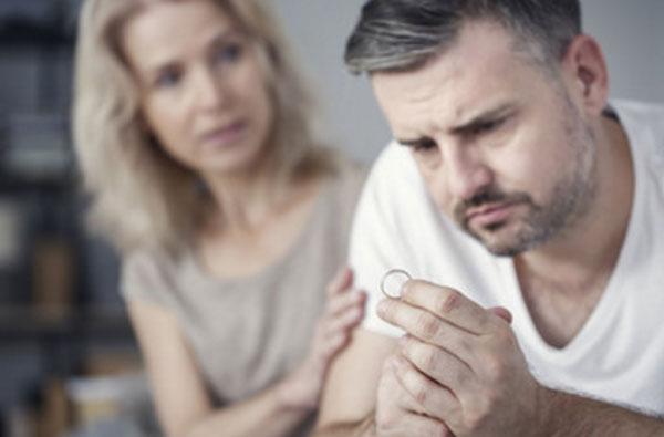 Мужчина держит кольцо в руке. Женщина сидит сзади него и держит за руку