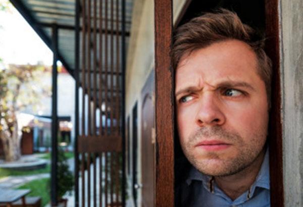 Мужчина приоткрыл дверь, выглядывает. Он напряжен