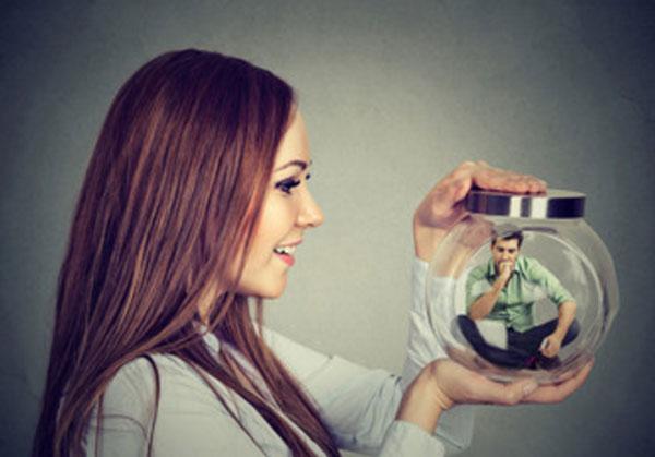 Женщина держит в руках емкость, внутри которой сидит миниатюрный мужчина