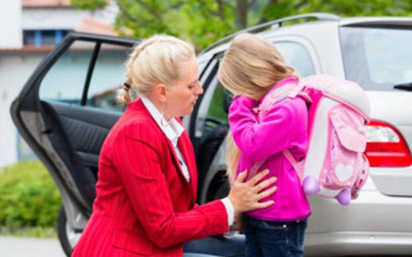 Девочка с рюкзаком на плечах плачет, мама ее успокаивает