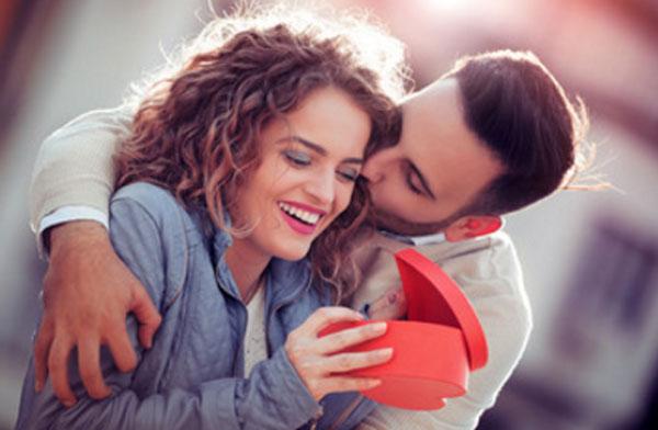 Девушка открывает коробочку в форме сердечка. Она очень рада. Парень обнимает ее и целует в щеку