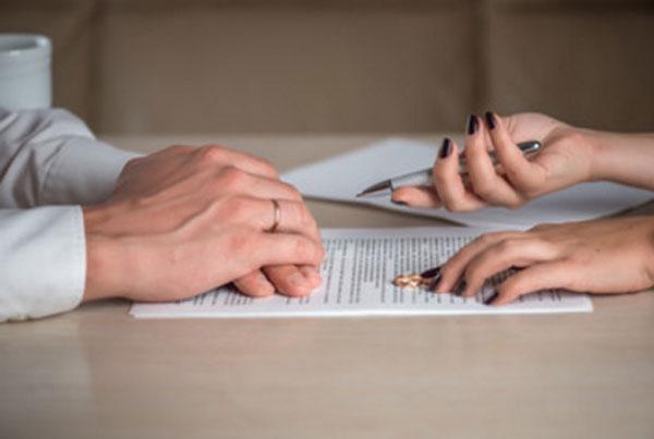 Женщина дает мужчине подписать бумаги на развод