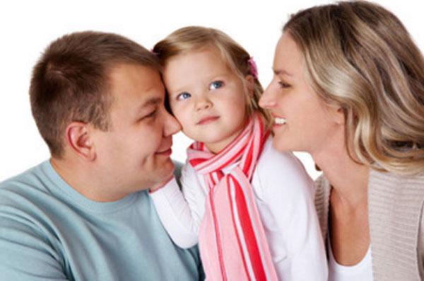 Маленькая девочка стоит между мамой и папой. Родители смотрят на нее и обнимают