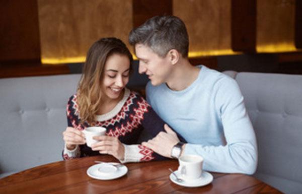 Пара сидит в кафе. Парень аккуратно обнимает девушку