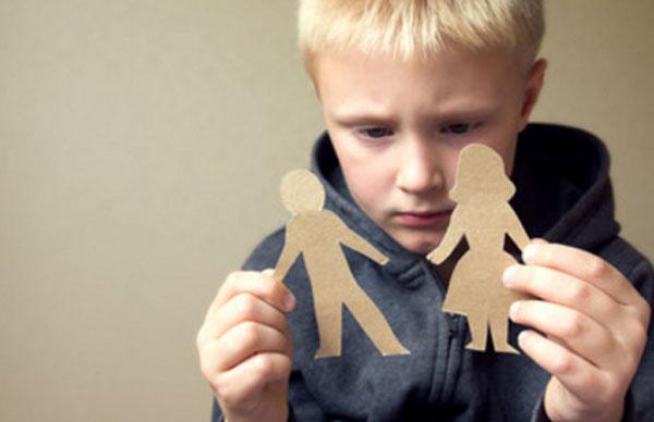 Мальчик держит в руках картонную фигурку мужчины и женщины. Он расстроен