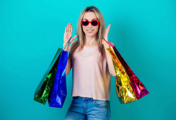 Женщина в солнцезащитных очках стоит с пакетами покупок