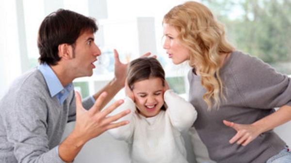 Девочка сидит между родителями, которые кричат друг на друга. Она закрывает руками уши.