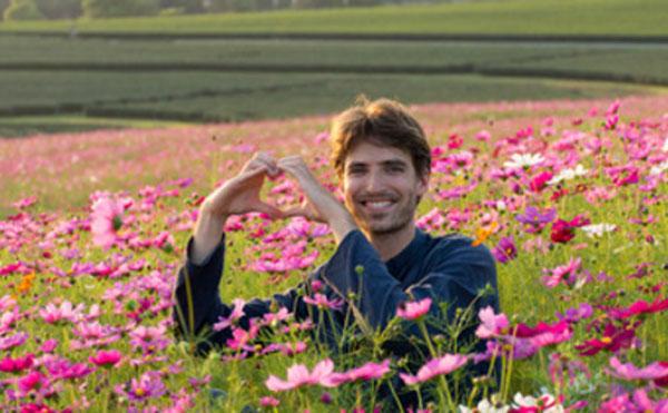 Мужчина сидит в цветах. Руками показывает форму сердца