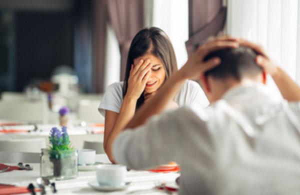 Пара сидит за столиком. Девушка в стрессовом состоянии, держится рукой за лицо. Мужчина наделал ошибок, схватился двумя руками за голову
