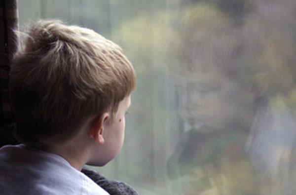 Грустный мальчик смотрит в окно