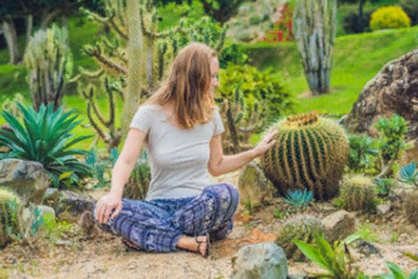 Девушка сидит в окружении кактусов и гладит их