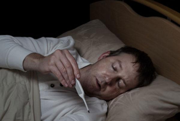 Больной мужчина в постели, смотрит на градусник