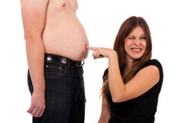 Торс пузатого мужчины. рядом его жена с отвращением тыкает пальцем в его живот