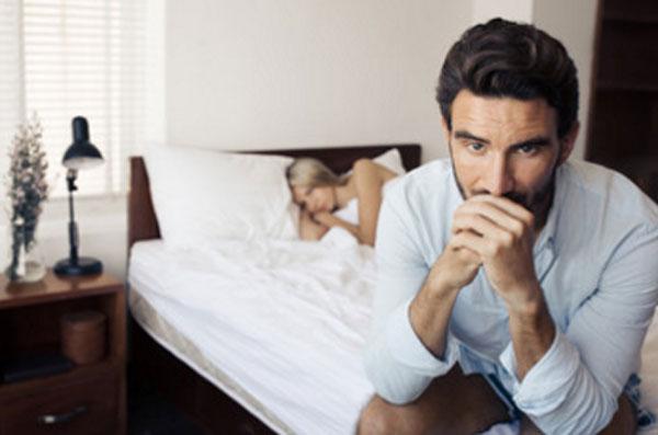 Мужчина сидит в задумчивости. на заднем плане спит его жена