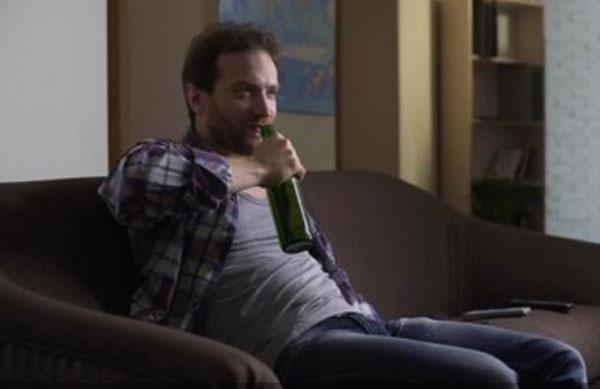 мужик с бутылкой в руках сидит на диване