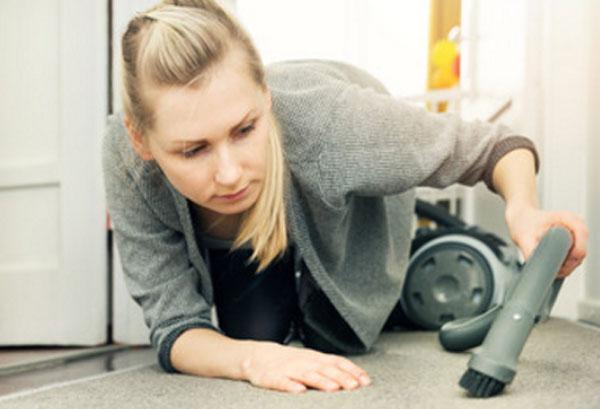 Женщина ползает по полу, чтоб тщательно пропылесосить ковер
