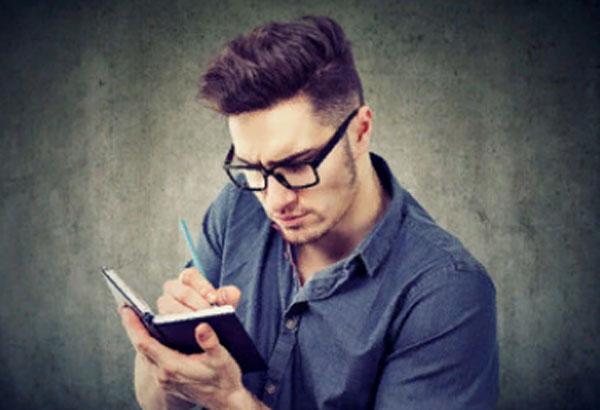 Мужчина в очках что-то сосредоточено записывает в свой блокнот