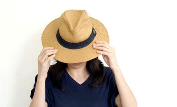 Девушка прячет лицо под шляпой