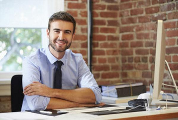 Улыбчивый мужчина сидит за рабочим столом, на котором полный порядок
