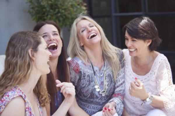 Четыре женщины сидят на одном диване. Две улыбаются, две смеются