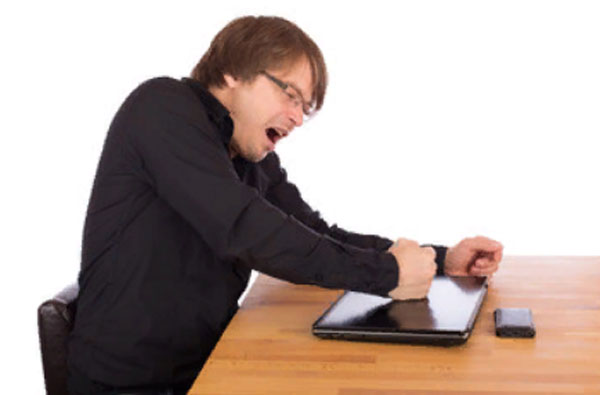 Вспыльчивый мужчина бьет кулаком по ноутбуку