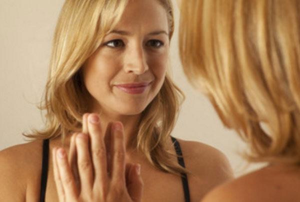 Женщина смотрит на свое отражение в зеркале, касаясь рукой ее отражения