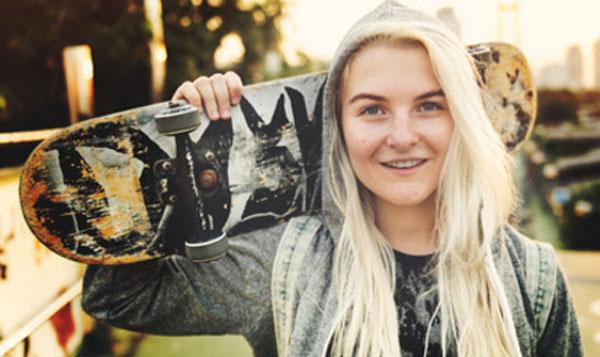 Веселая девушка - подросток со скейтом в руках