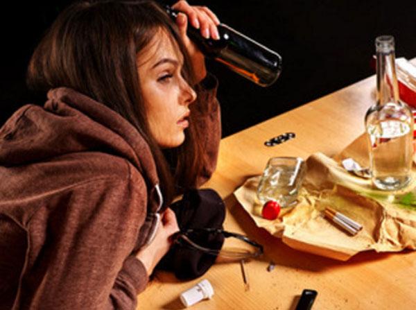 Девушка с бутылкой в руке. На столе пустая бутылка от спиртного, сигареты, таблетки