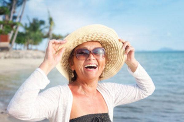Женщина в шляпке идет по берегу и смеется