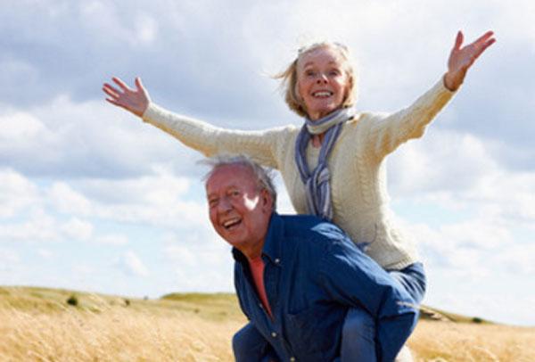 Пожилой мужчина держит на спине пожилую женщину. Оба счастливы