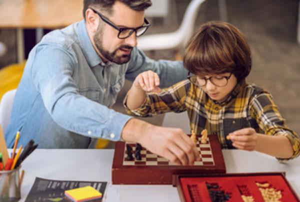 Мужчина в очках объясняет мальчику в очках, как играть в шахматы