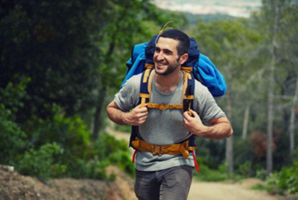 Мужчина с походным рюкзаком на спине. Он счастлив