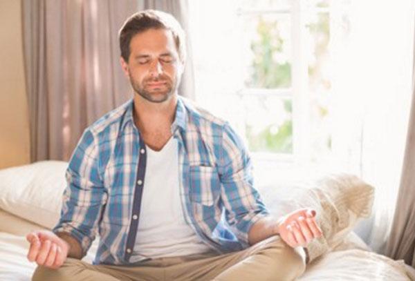 Спокойный мужчина сидит в позе йога на диване