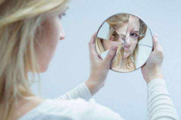 Девушка с комплексами смотрит на свое отражение в разбитом зеркальце