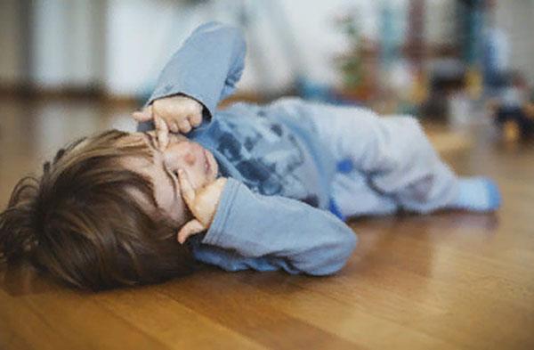 Ребенок лежит на полу и трет заплаканные глаза