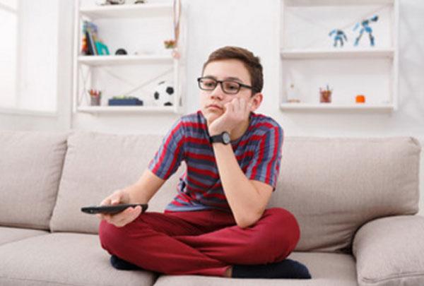 Мальчик в очках с пультом в руках сидит на диване