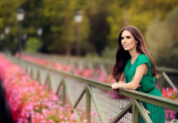 Счастливая женщина стоит на мосту