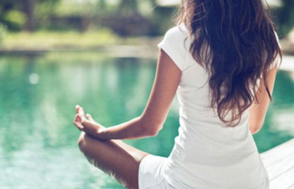 Женщина сидит у реки в позе йога
