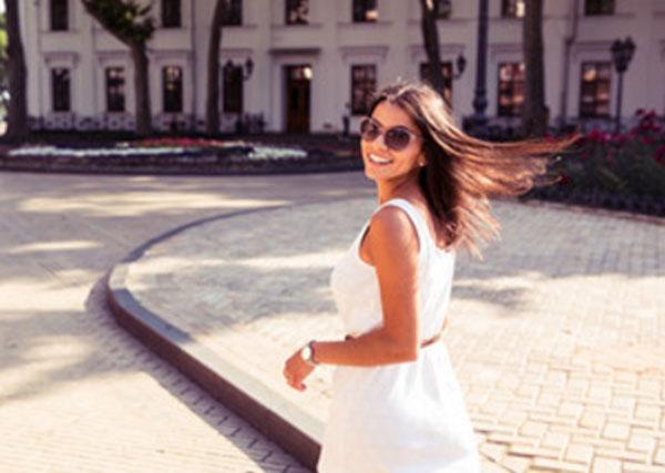 Счастливая девушка в солнцезащитных очках на прогулке