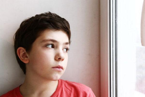Мальчик сидит у окна и грустно в него смотрит
