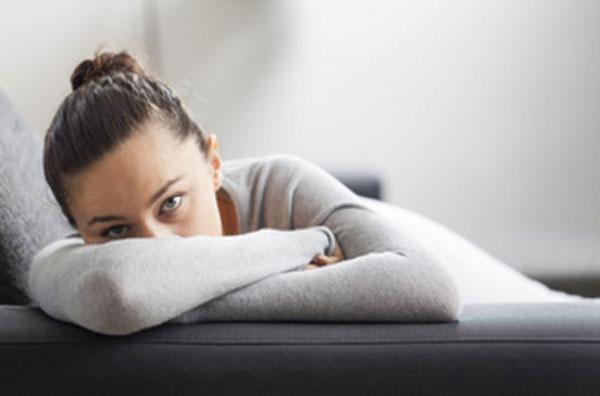 Женщина лежит на диване. Руки скрещены, лицо прячется за ними