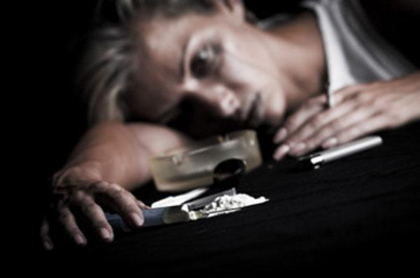 Женщина в плохом состоянии положила голову на стол. Перед ней порошок