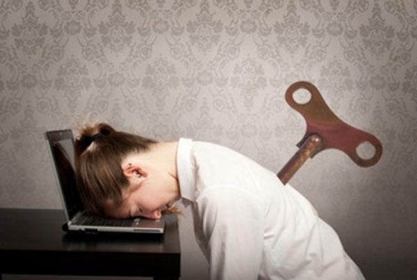 Женщина с ключом в спине положила голову на ноутбук