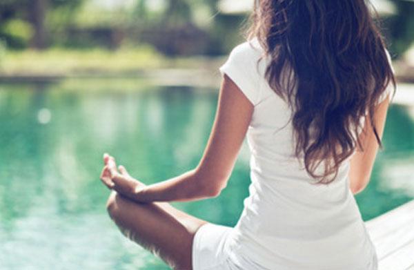 Девушка умиротворенно сидит возле водоема