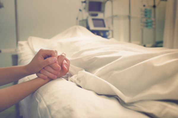 Умерший человек в палате больницы, накрытый простыней. Кто-то держит умершего за руку