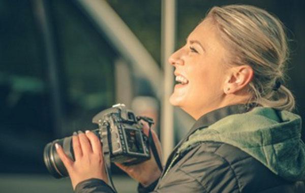 Женщина с фотоаппаратом в руках. Она смеется