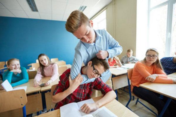 Один ученик схватил за голову другого, сидящего за партой