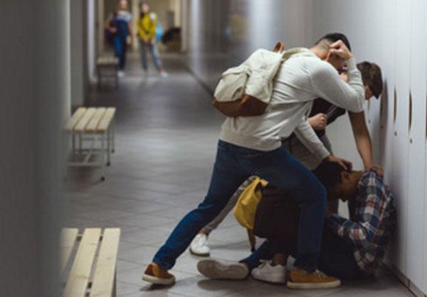 Мальчика избивают одноклассники в школьном коридоре